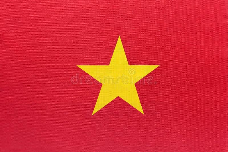 Nationell tygflagga i Vietnam med emblem, textilbakgrund fotografering för bildbyråer