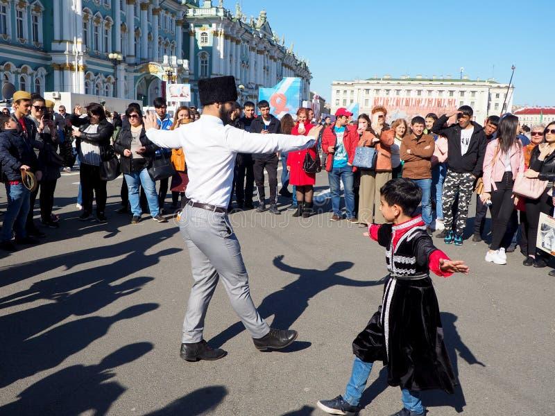 Nationella danser av barn och vuxna m?nniskor p? fyrkanten i staden arkivfoton