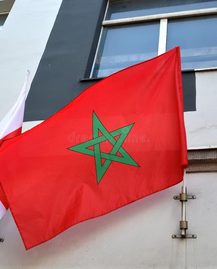 Nationsflaggan av Konungariket Marocko fladdrar på en byggnadsfasad arkivfoto