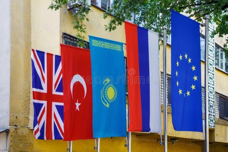 Nationsflaggan av Republikenet Kazakstan är bredvid nationsflaggorna av Förenade kungariket, Turkiet, Ryssland arkivbild