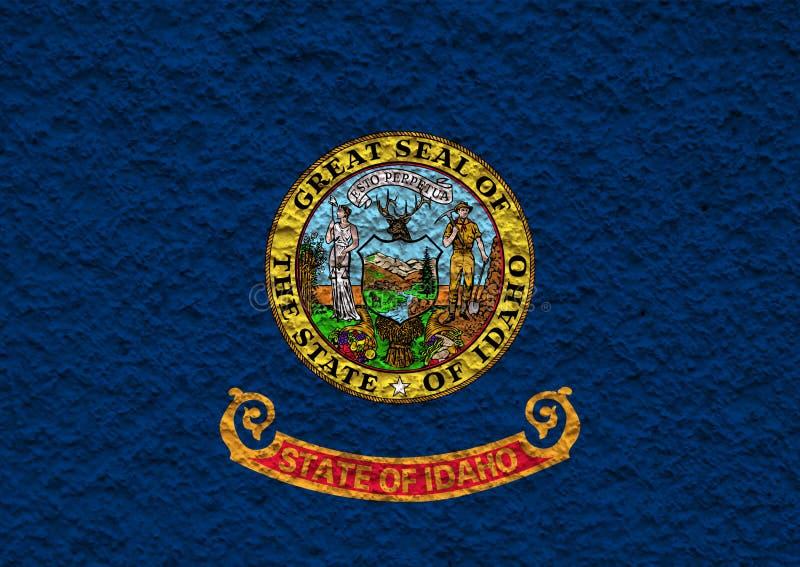 Nationsflaggan av USA-staten Idaho in mot en grå vägg med stenig yttersida på dagen av självständighet i färg av blått rött arkivbild