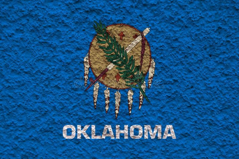 Nationsflaggan av USA-staten Oklahoma in mot en grå vägg med stenig yttersida på dagen av självständighet i färger av blått royaltyfri foto