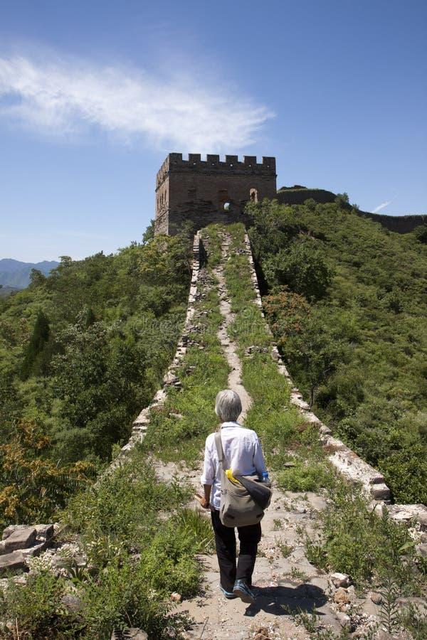 Nativ-Frau, die auf Chinesische Mauer geht lizenzfreie stockfotos