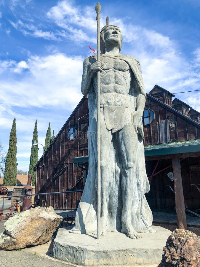 Native American with arrow statue. This stature of a native American with an arrow is made of concrete and it is located in Elk Gove California and it is one of stock photography