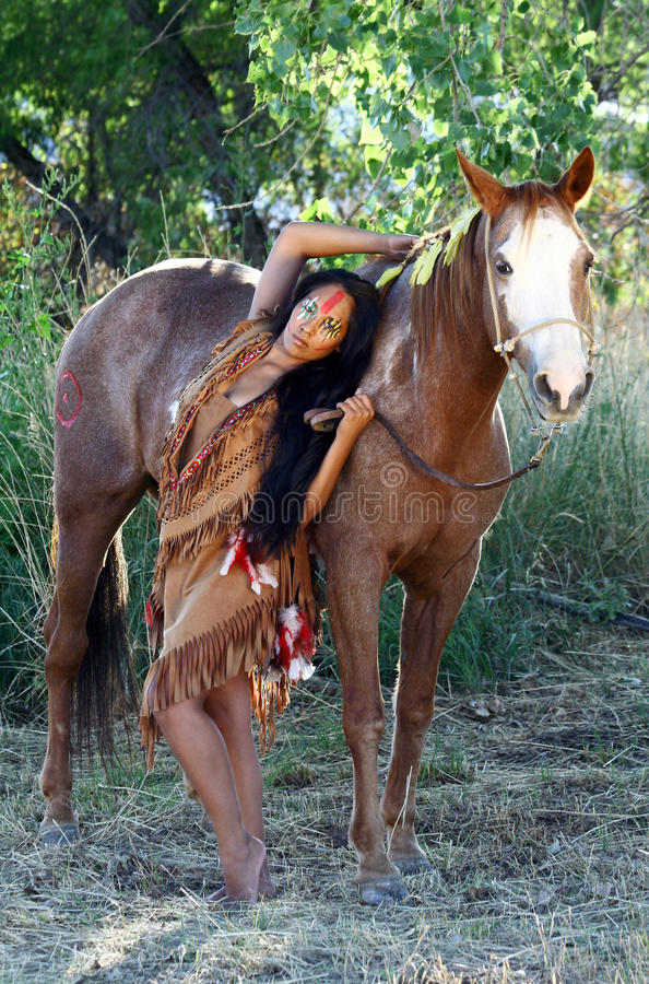 Native American and Her Horse. A Native American woman stands next to her horse stock images
