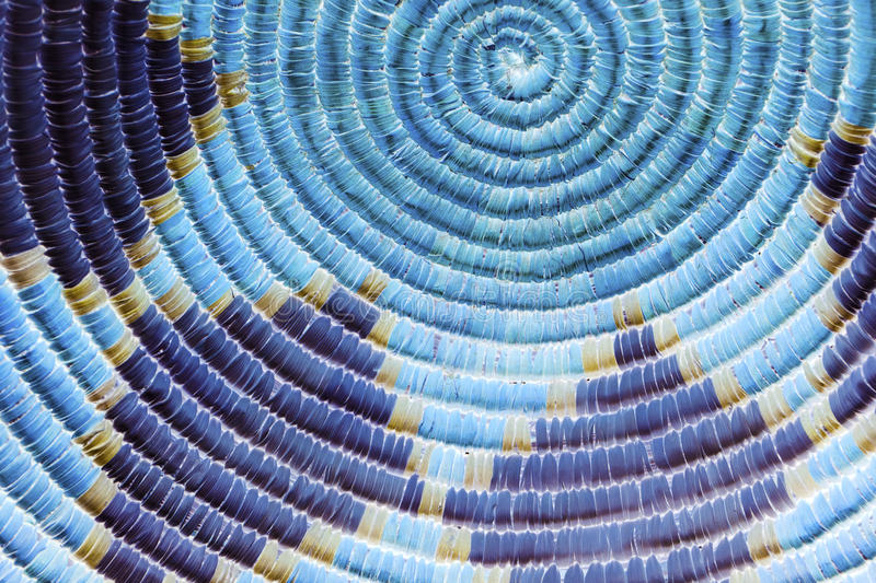 Native American Indian Basket Detail in Blue. A close up photo of an indian basket with rich straw textures, circular patterns and colorful shapes royalty free stock image
