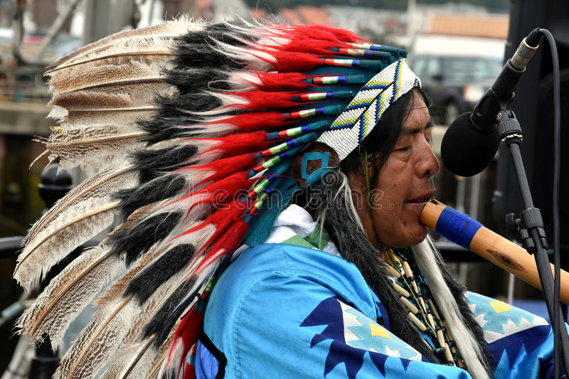 Native american indian plays flute. Native American Indian tribal group play music and sing on the street in historical city of Whitby ,United Kingdom, England