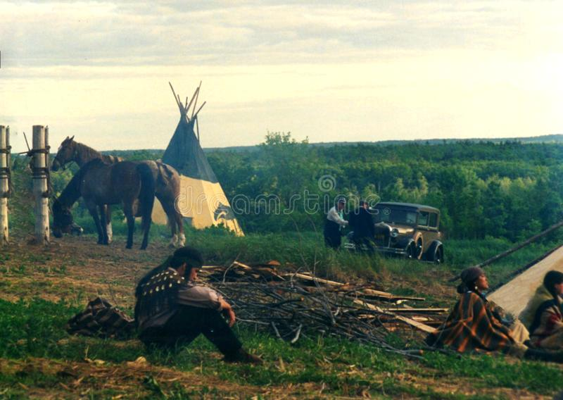 Native American indian sitting on the ground. In the Village with tee pee and horses stock images