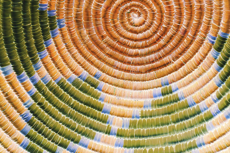 Native American Indian Textures in Orange and Green. A close up photo of an indian basket that has a colorful, circular pattern and straw textures, inverted to a stock photography