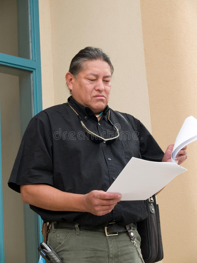 Native American man glancing at papers. Native American man stepping out of an office building and reading papers royalty free stock image