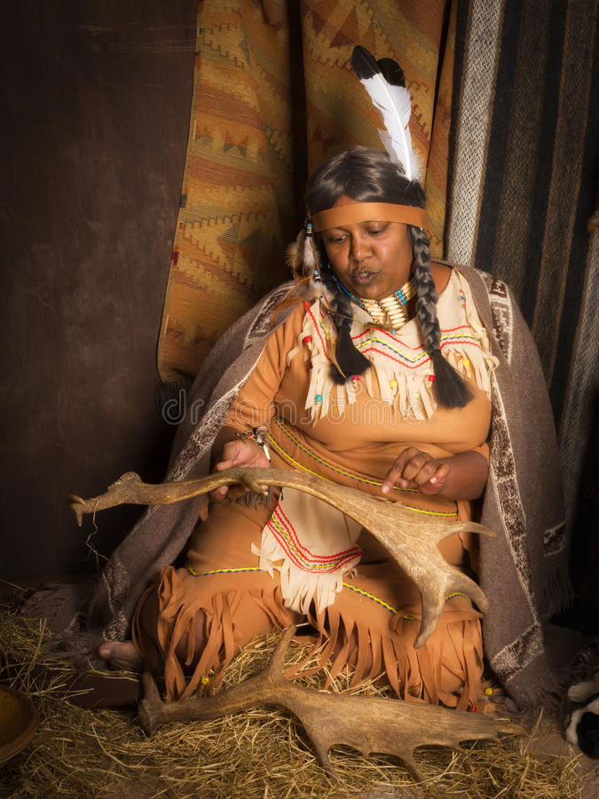 Native American storyteller. Weathered mature tribal female storyteller talking about heroic times stock photography
