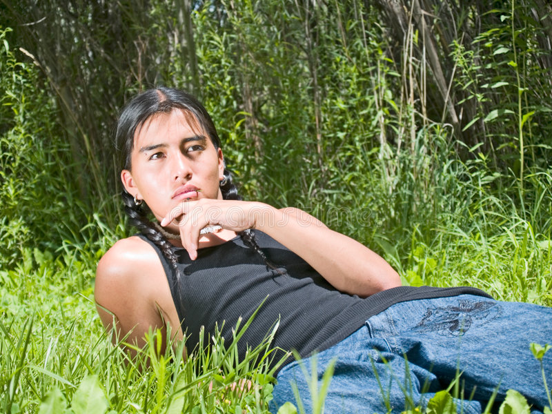 Native American teenage boy. Handsome 15 year old Native American boy relaxing on lawn stock images