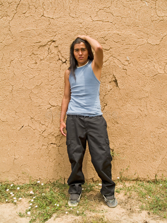 Native American teenage boy. Portrait of a handsome 15 year old Native American boy by an adobe wall stock photo