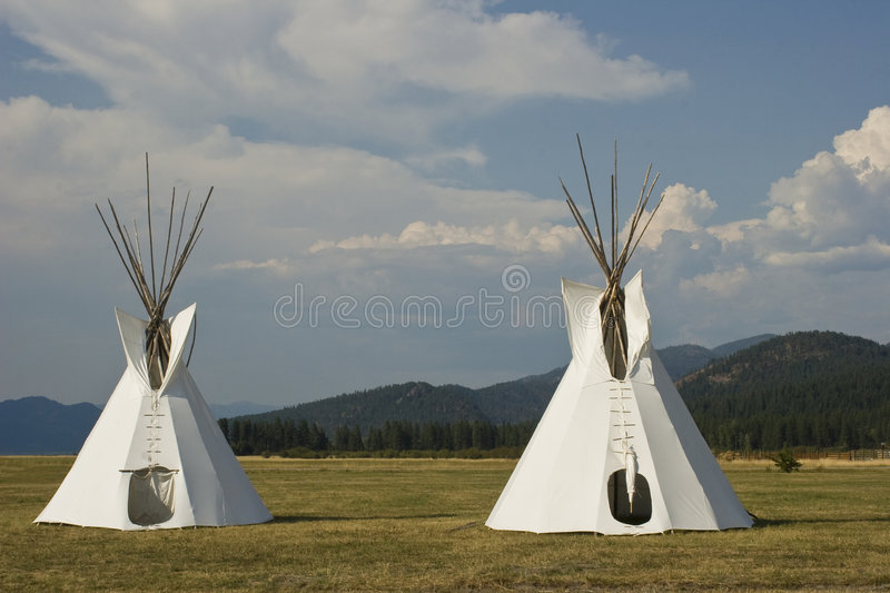 Native American Teepee Village. Two Native American Teepees on grass in front of wooded hills royalty free stock image