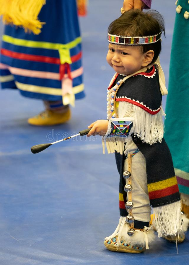 Native American Toddler Wearing Full Pow Wow Regalia. An unhappy Native American male toddler with fringed shawl and loin cloth, beaded mocassins and headband royalty free stock photo