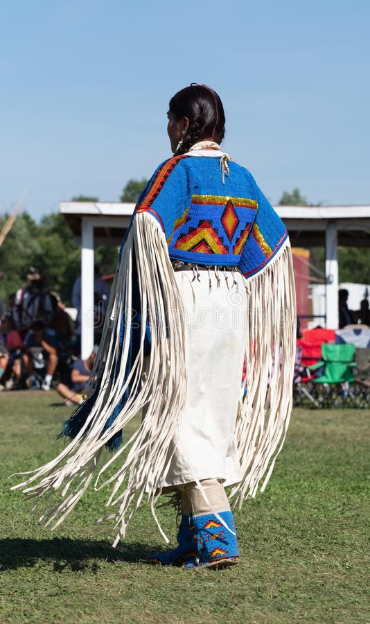 Native American Woman Dancing at Pow Wow with Fringed Dress. Native American woman dancing at a pow wow with a leather dress with fringed sleeves and ornate royalty free stock images