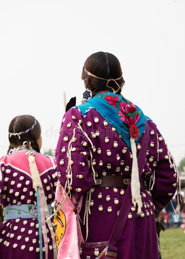 Native American Woman and Girl in Elk Tooth Dresses. With purple fabric and  beaded headbands at a pow wow. Photographed from behind royalty free stock image