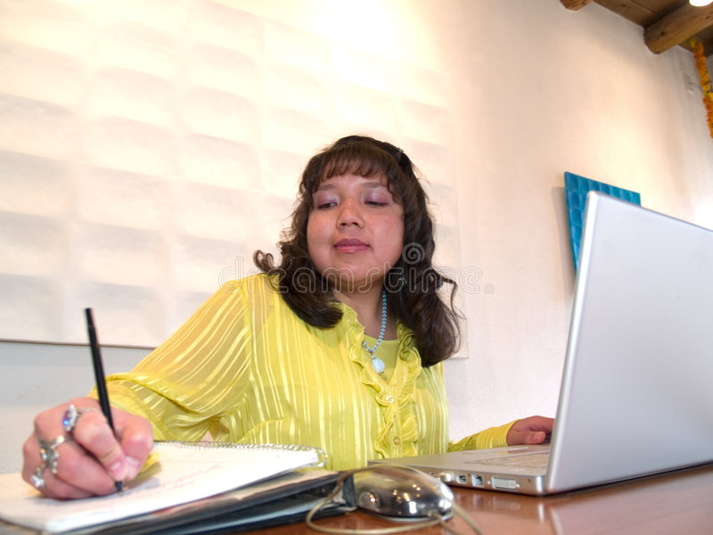 Native American woman at office. Native American woman working on a laptop in her office royalty free stock image
