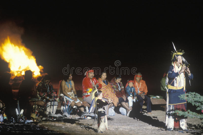 Native Americans in costume by bonfire. Watching flautists during 65th annual intertribal ceremony in Gallup, NM stock image