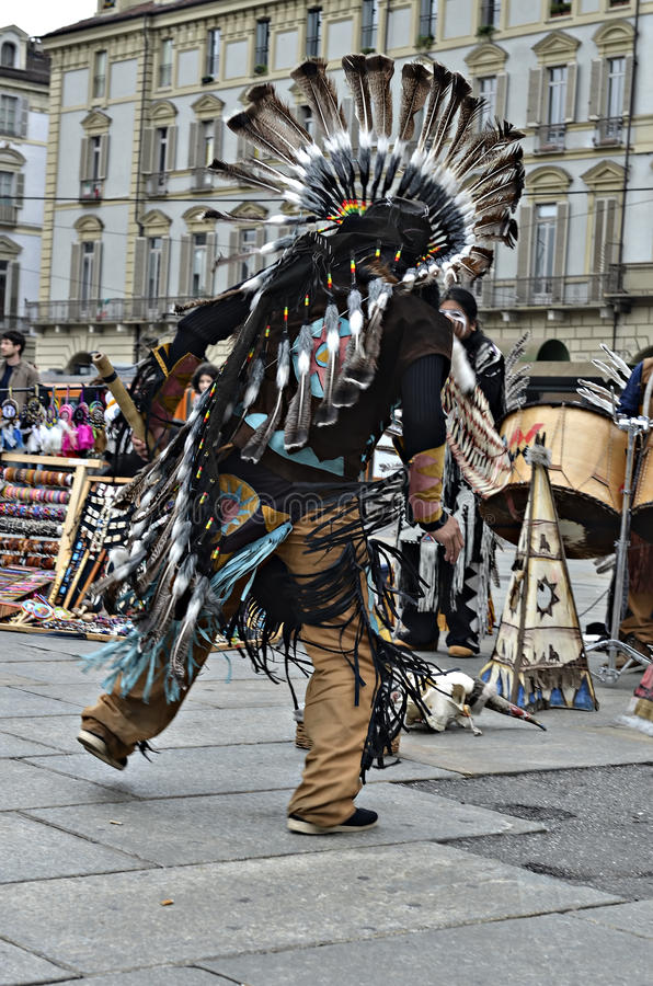 Native Americans dancing in street. Turin, Italy - April 27, 2013: Red indian in traditional costume dancing in the center of Turin, Italy. Street performance of royalty free stock photos