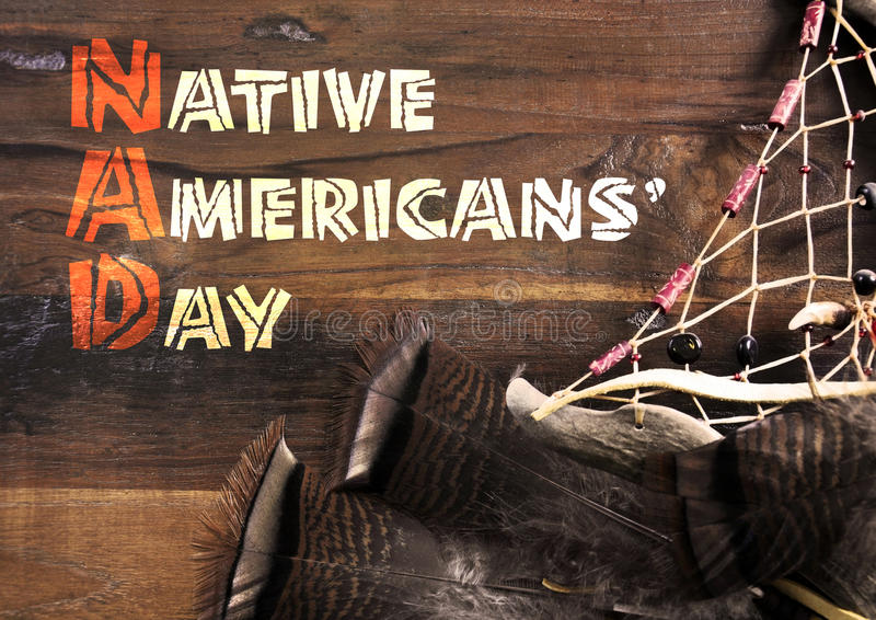 Native Americans Day greeting on wood with dream catcher. Native Americans Day wood carving style greeting text on dark rustic recycled wood background with stock photo