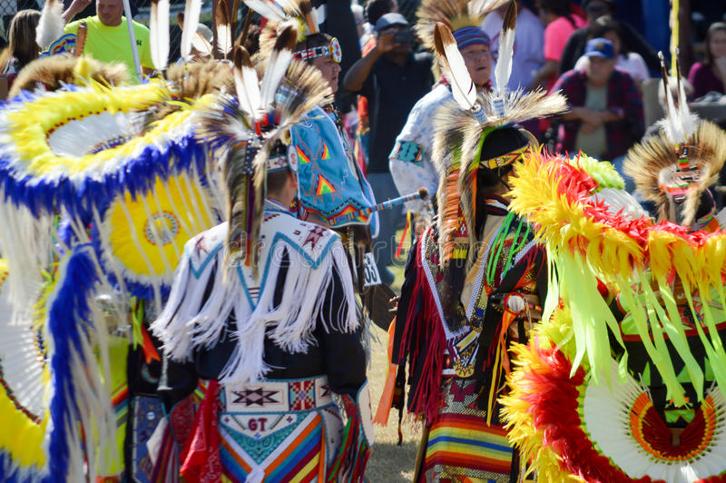 Native Americans in Feather costumes. Native Americans wearing bright colored feather costumes at powwow dance competition royalty free stock photography