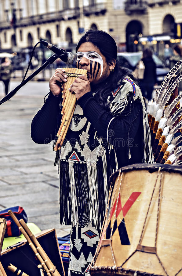 Native Americans street musician. Turin, Italy - April 27, 2013: Red indian in traditional costume plays in the center of Turin, Italy. Street performance of a royalty free stock photography