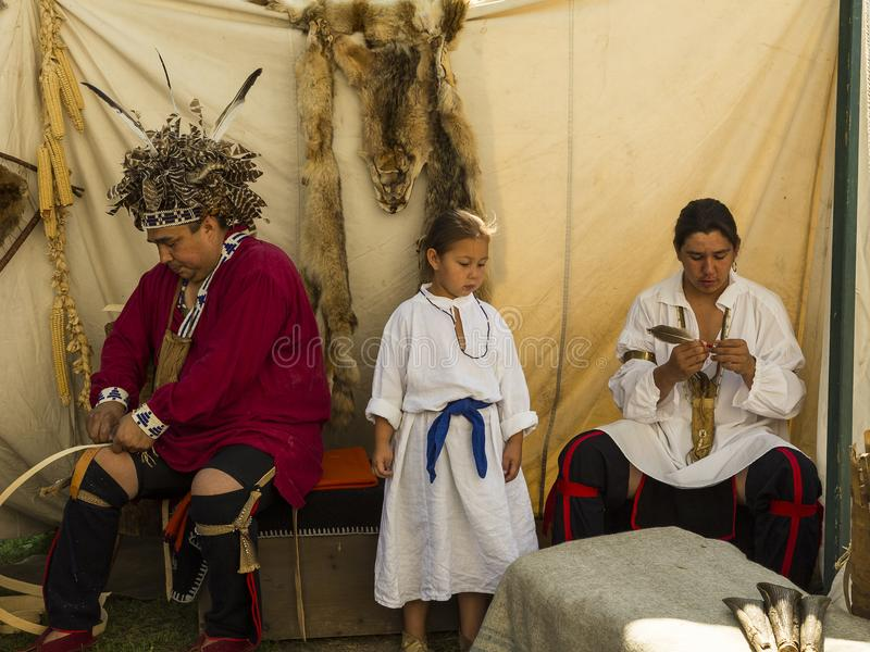Native family participating in a demonstration of traditional crafts. During a fair held in Old Montreal, Montreal, Quebec, August 25, 2013 royalty free stock image