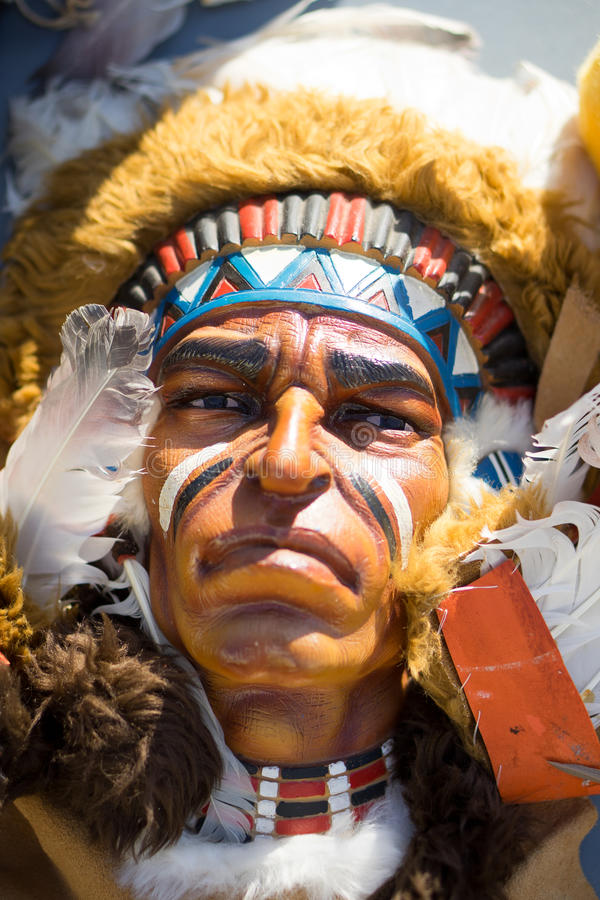Native Indian. A close up view of a decorative face of an American Indian. The Indian is wearing a war bonnet, made up of feathers, and is usually only worn by