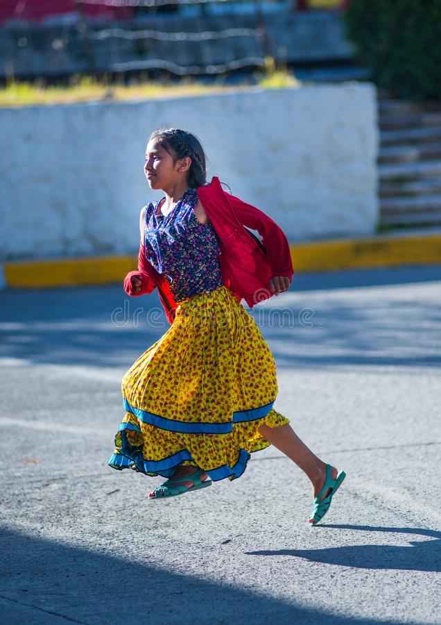 Native Indigenous girl run in traditional colorful dress on city street with a smile, Mexico, America. A Native Indigenous or Indian school girl running on royalty free stock image