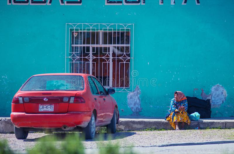 Native Indigenous old lady in traditional dress in colorful city street with car, in Mexico, America royalty free stock image