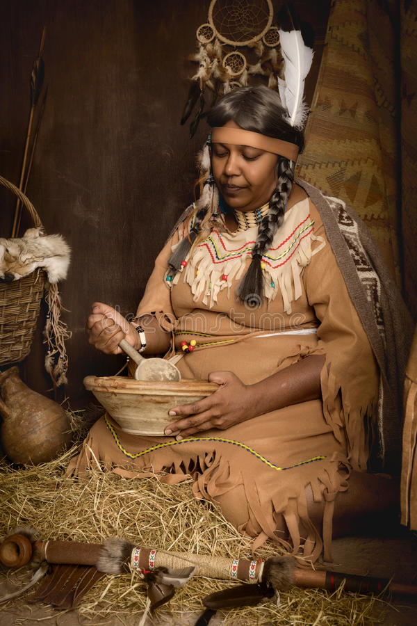 Native old squaw. Weathered mature tribal female storyteller talking about heroic times royalty free stock photography