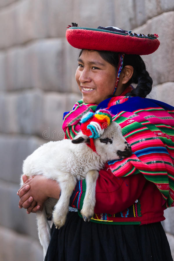 Native Peruvian holding a baby lamb. Cusco, Peru - May 14 : Jenni, a young woman dressed in colorful traditional native Peruvian closing holding a baby Lamb with royalty free stock photos