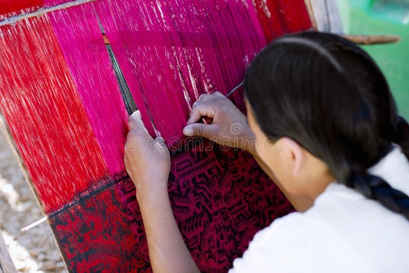 Native Peruvian woman weaving intricate llama wool garments. Using a traditional hand loom royalty free stock image