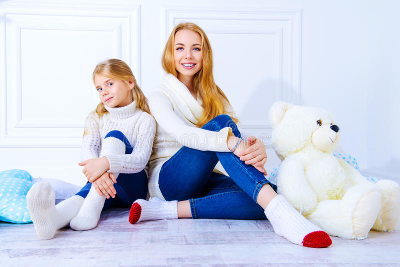 Native sisters. Family portrait. Two cute girls, older and younger sister sitting together. Children`s fashion, winter style stock images