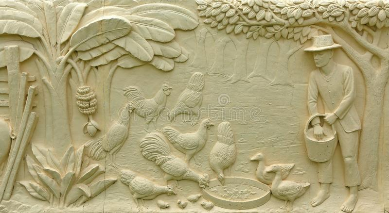 Native Thai culture stone carving on temple wall stock photos