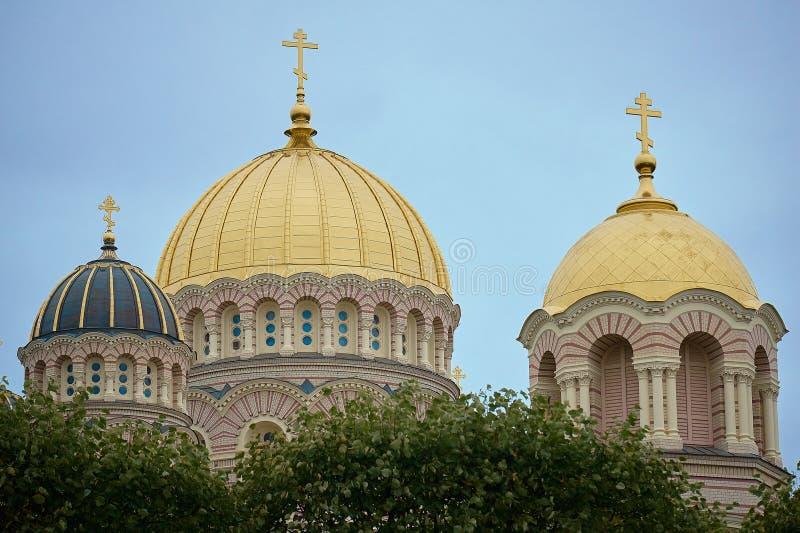 Nativité de Riga de cathédrale du Christ - église et point de repère célèbres Fermez-vous des dômes jaunes d'or sur Sunny Sky Bac photo libre de droits