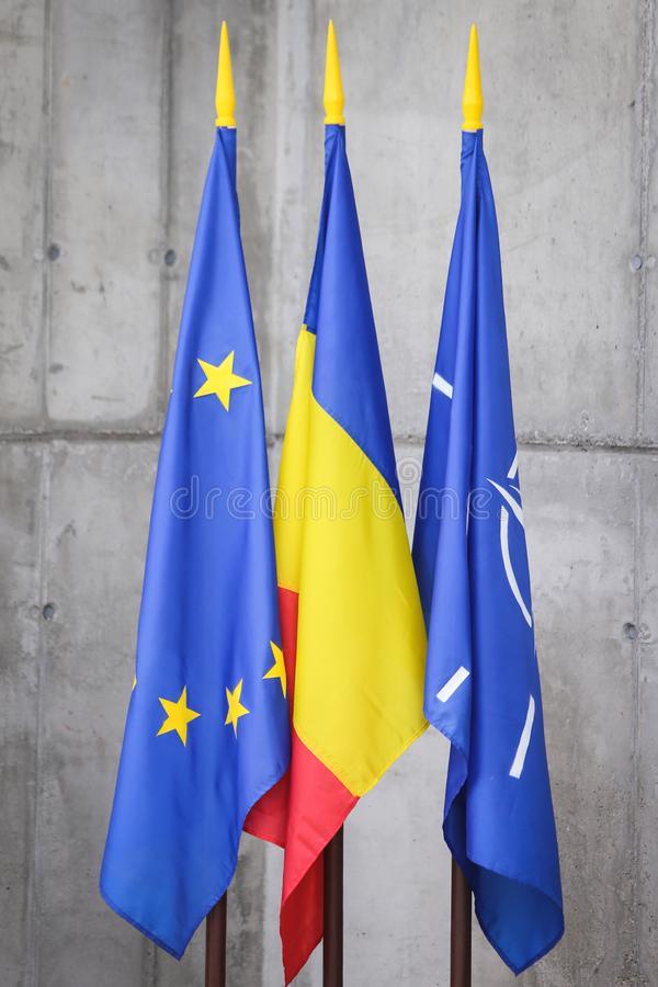 NATO, Romania and European Union flags. On a rough concrete background stock image
