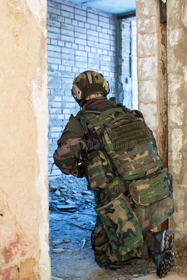 NATO soldier in full gear. Soldier with a gun standing on one knee In an ambush in a doorway inside destroyed building royalty free stock image
