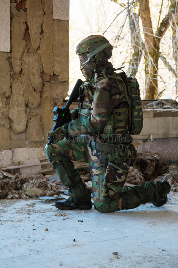 NATO soldier in full gear. Soldier with a gun standing on one knee, looking into the window opening inside destroyed building royalty free stock image