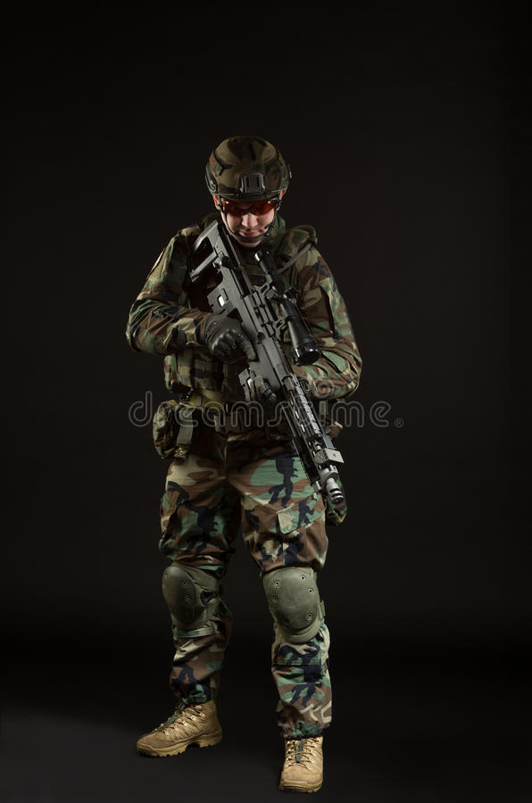 NATO soldier in full gear. Military man over black background stock images