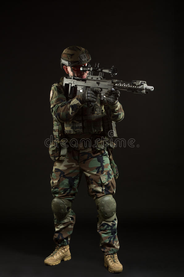 NATO soldier in full gear. Military man over black background stock photos