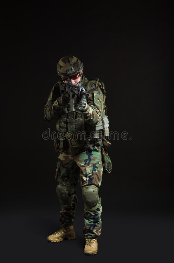 NATO soldier in full gear. Military man over black background royalty free stock photo