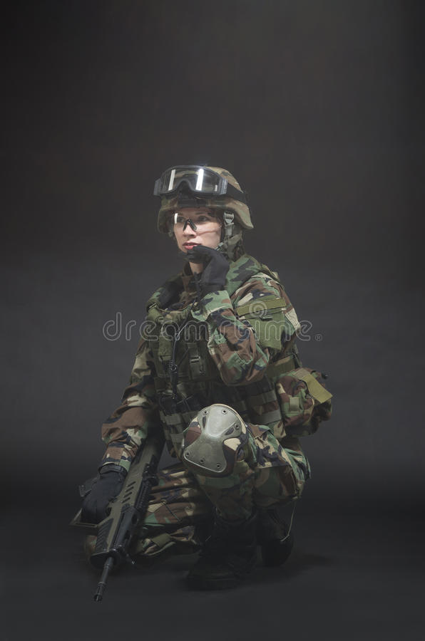 NATO soldier in full gear. Military woman over black background royalty free stock image