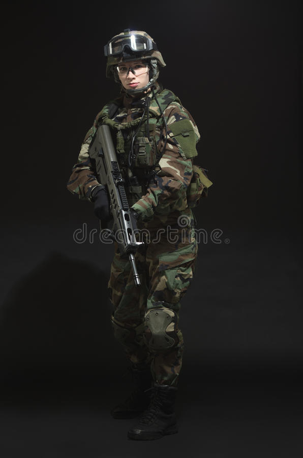 NATO soldier in full gear. Military woman over black background stock images