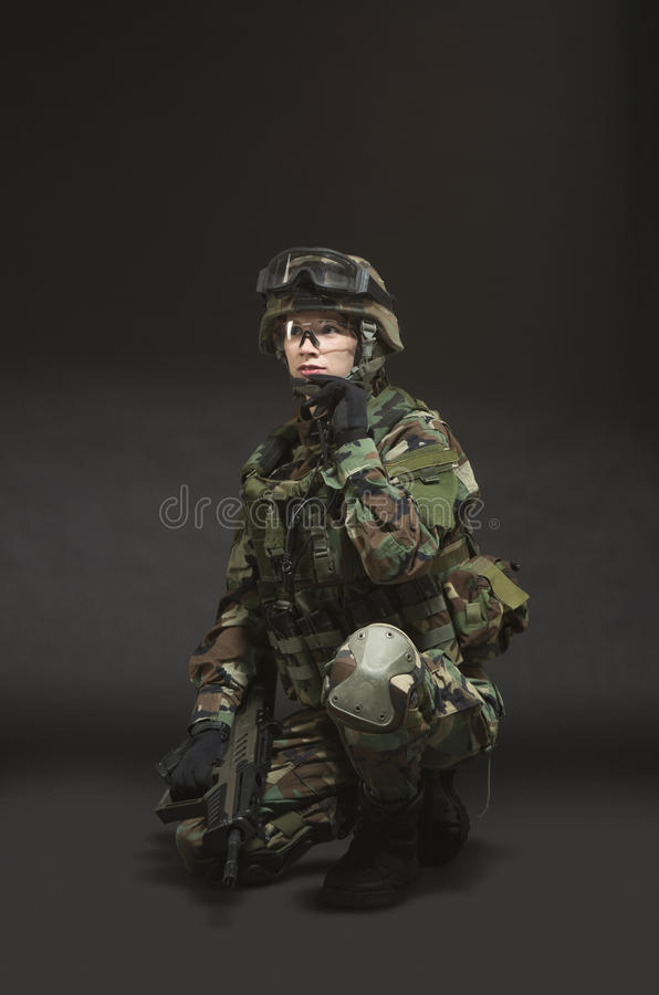 NATO soldier in full gear. Military woman over black background stock photos
