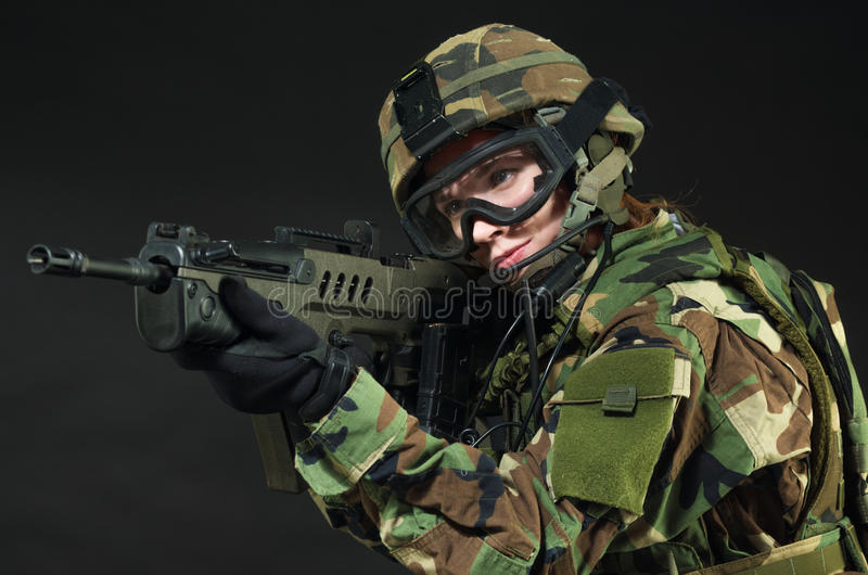 NATO soldier in full gear. Military woman over black background royalty free stock photo