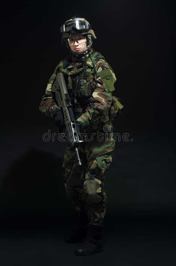 NATO soldier in full gear. Military woman over black background royalty free stock photography
