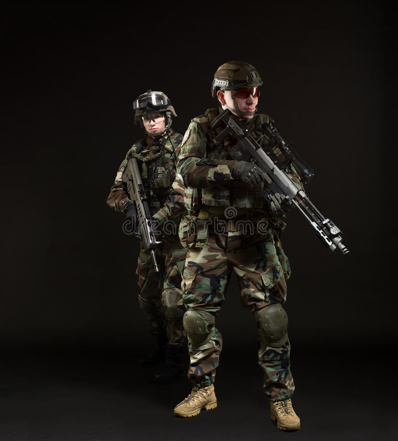 NATO soldier in full gear. NATO soldiers in full gear. Military men anв women over black background royalty free stock photography