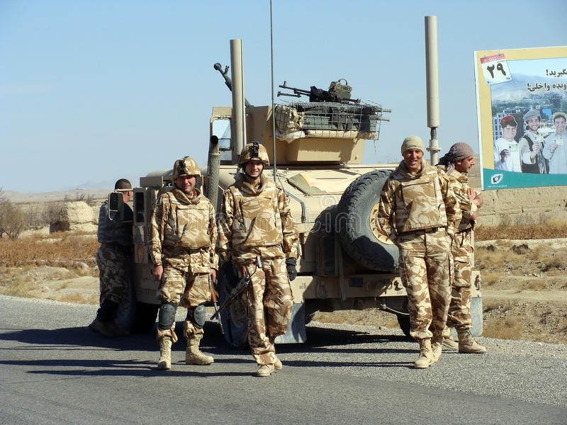 Nato soldiers in Afghanistan. This image represents 4 Nato soldiers patrolling in Afghanistan. This image can be used to associate a picture with what the royalty free stock photos